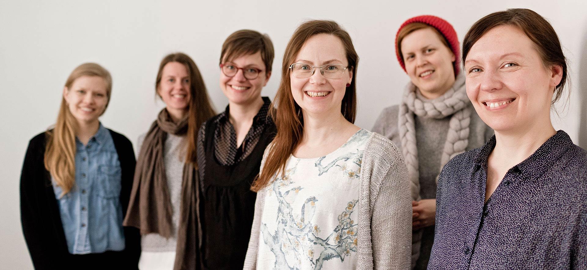 Joukko Noon-kollektiivin jäseniä hymyilee ryhmäkuvassa