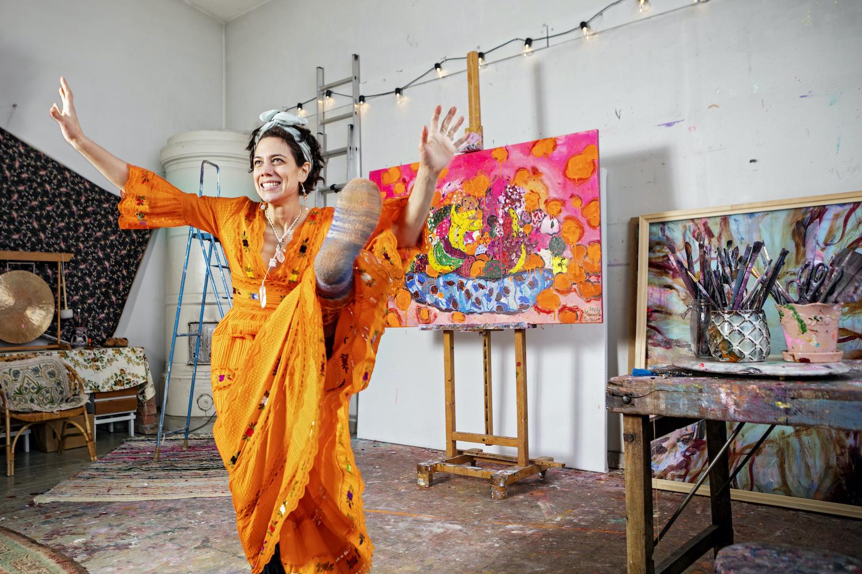 Värikkääseen asuun pukeutunut Manuela Bosco ateljeessa. Taustalla tauluja, takka ja maalaustarvikkeita.